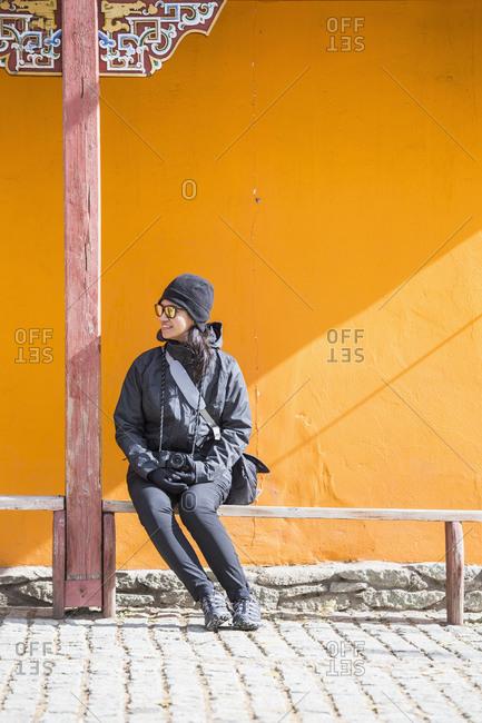 Tourist taking break on bench, Ulaanbaatar, Mongolia