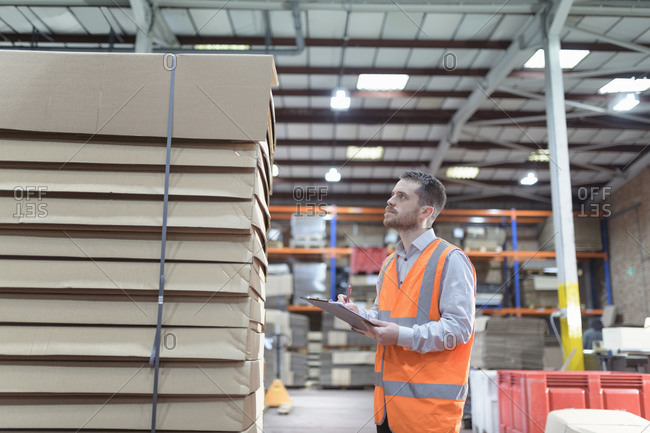 Worker inspecting boxes in cardboard box factory