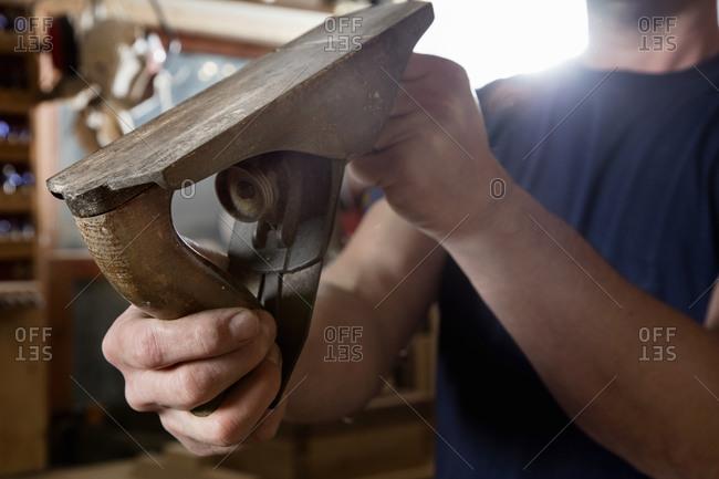Craftsman holding wood plane in workshop