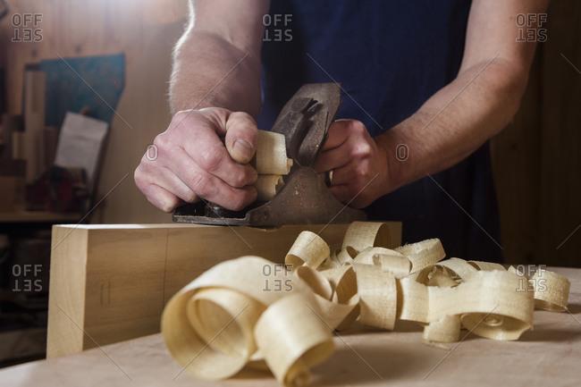 Craftsman using wood plane in workshop