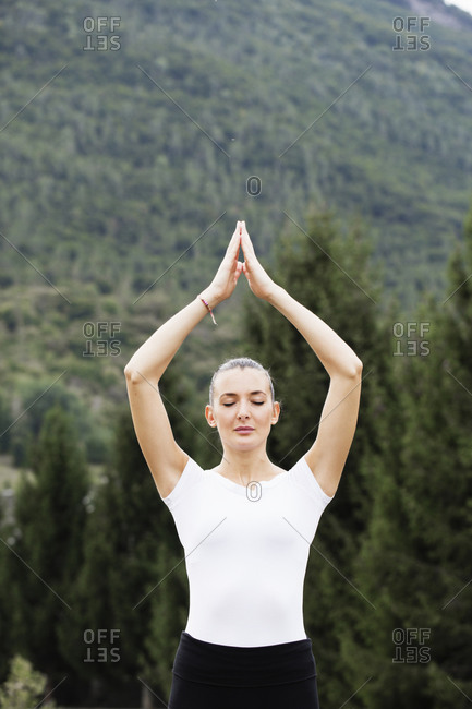 Woman practicing yoga, eyes closed and hands together