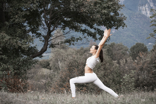 Woman practicing yoga, warrior pose in rural landscape