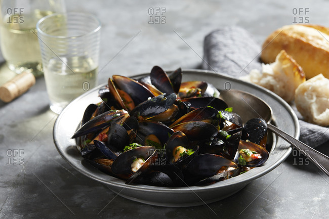 Bowl of garlic mussels with glass of white wine