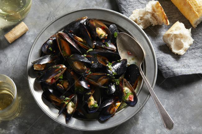Bowl of garlic mussels with glass of white wine, overhead view