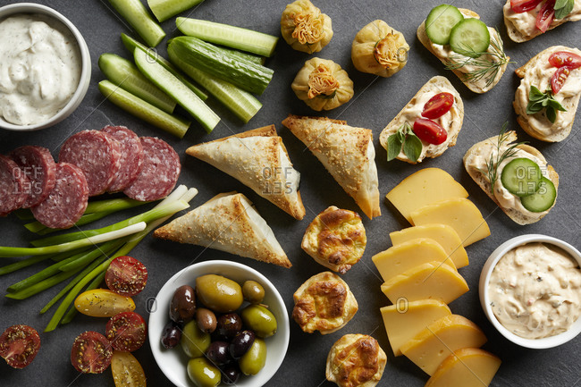 Appetizer snack spread with open sandwiches, olives and cheese , overhead view