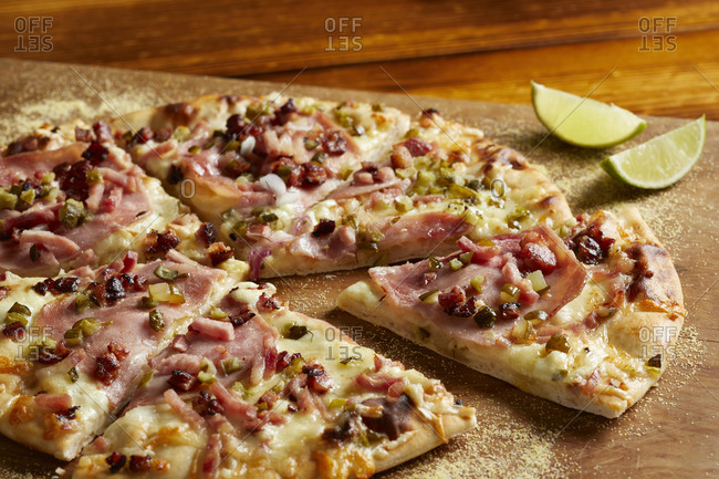 Cuban ham & swiss pizza with lime on chopping board