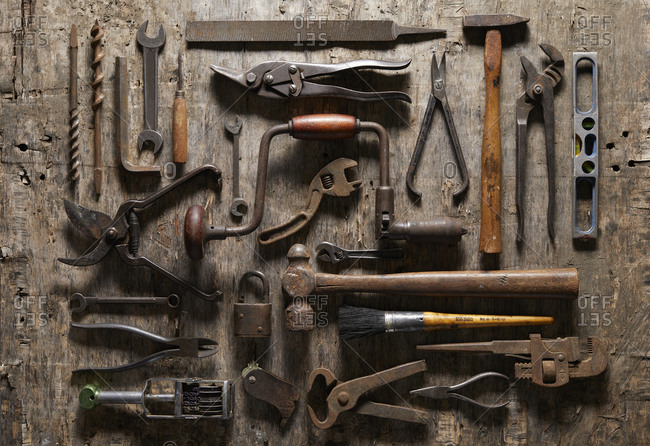 Variety of vintage hand tools on wood, overhead view