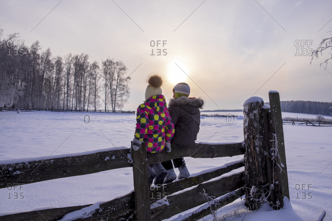 Boy and girl sitting on fence in snow covered landscape, rear view
