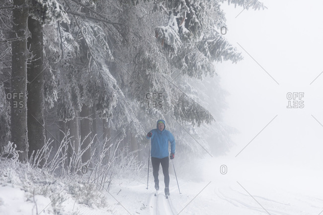 Mature man cross country skiing by misty forest, full length