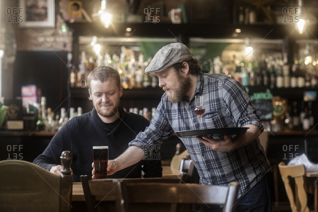 Barman serving beer to customer in traditional Irish public house