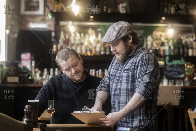 Barman looking at menu with customer in traditional Irish public house
