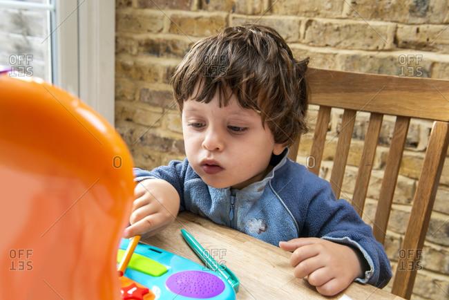 Toddler boy using toy laptop