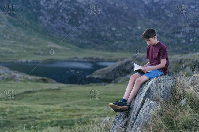 Boy reading book on hilltop, Snowdome, Llanberis, Gwynedd, UK