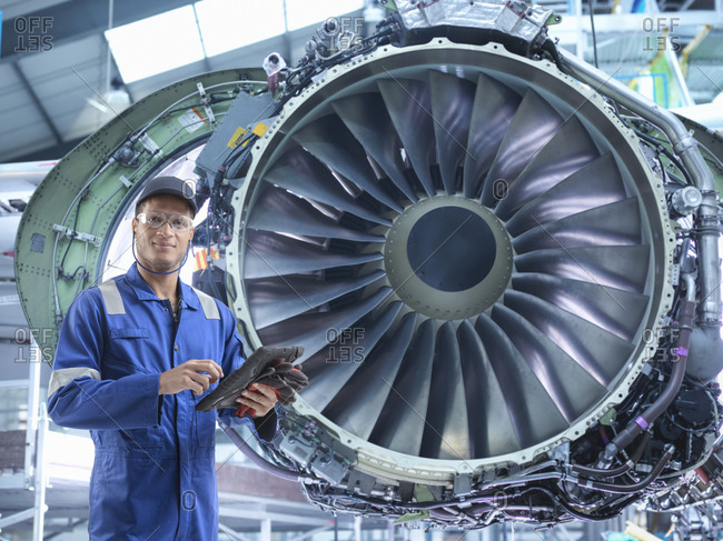 Composite image of engineer with jet engine in aircraft maintenance factory