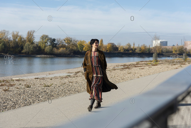 Woman walking along Rhine River, Strandbad, Mannheim, Germany