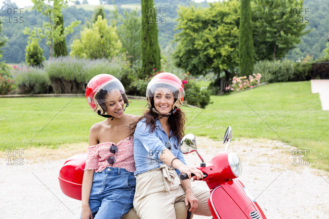 Women on scooter in countryside, Cite della Pieve, Umbria, Italy