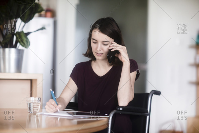 Woman in wheelchair using cellphone and taking notes