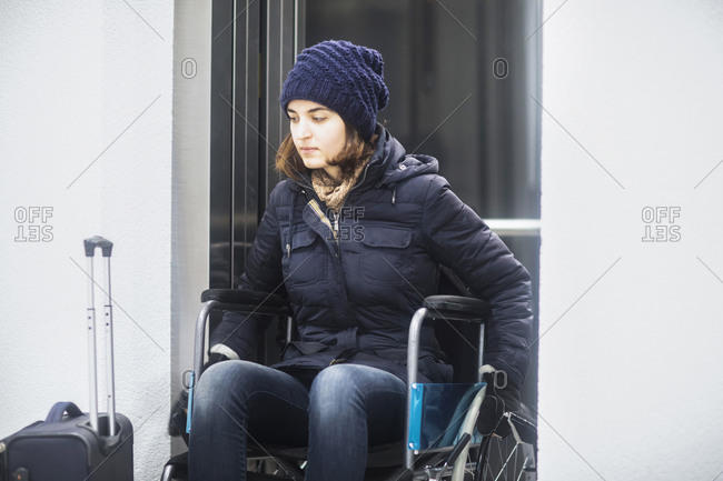 Woman in wheelchair with luggage