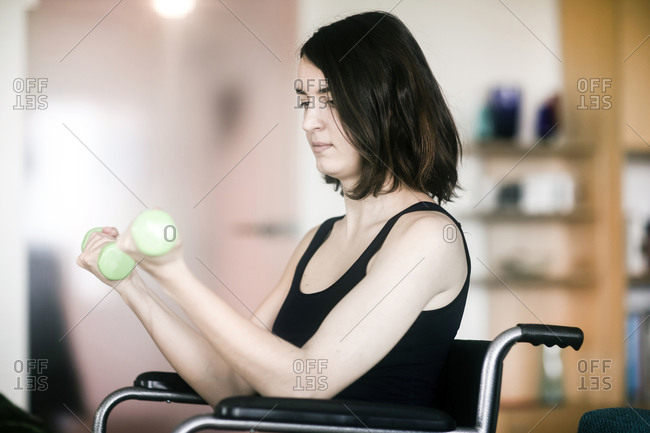 Woman in wheelchair using weights at home