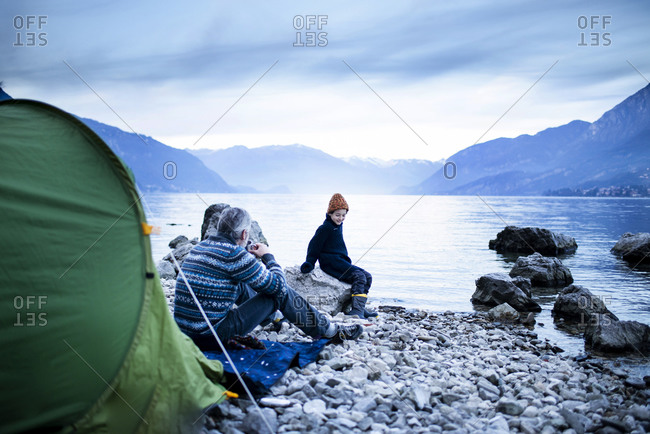 Father and son camping by lakeside, Onno, Lombardy, Italy