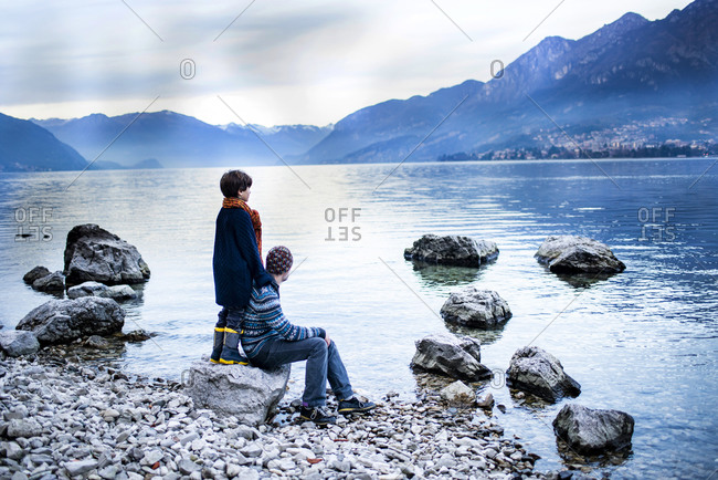 Father and son on lakeside, Onno, Lombardy, Italy