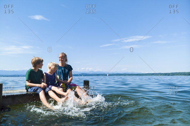 Mother and children cooling feet in water, Lake Starnberg, Bavaria, Germany