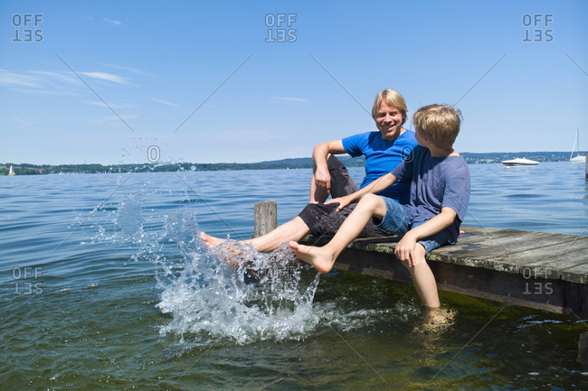 Father and son cooling feet in water, Lake Starnberg, Bavaria, Germany