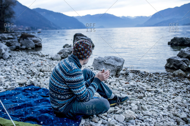 Man camping on lakeside, Onno, Lombardy, Italy