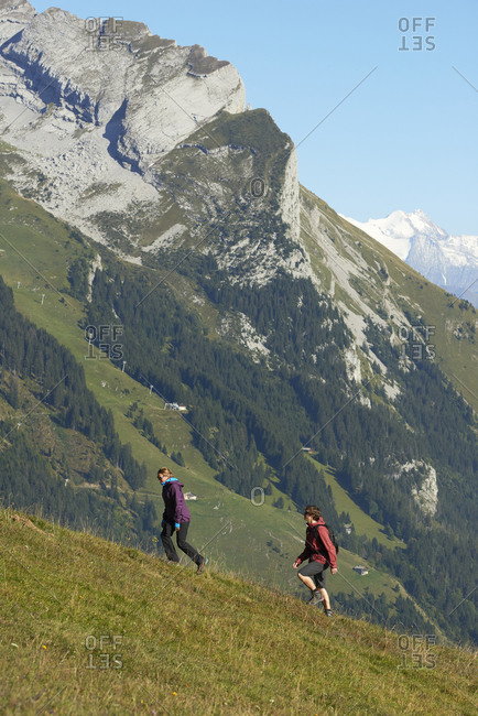 Hikers trekking on hillside, Manigod, Rhone-Alpes, France