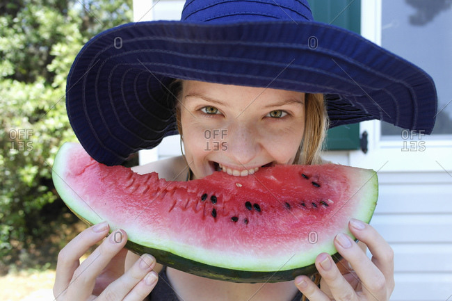 Woman biting into watermelon