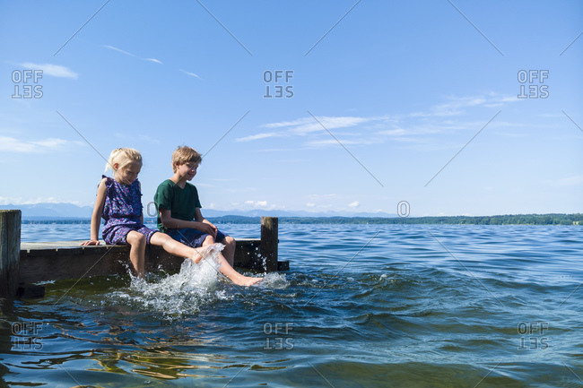 Siblings cooling feet in water, Lake Starnberg, Bavaria, Germany