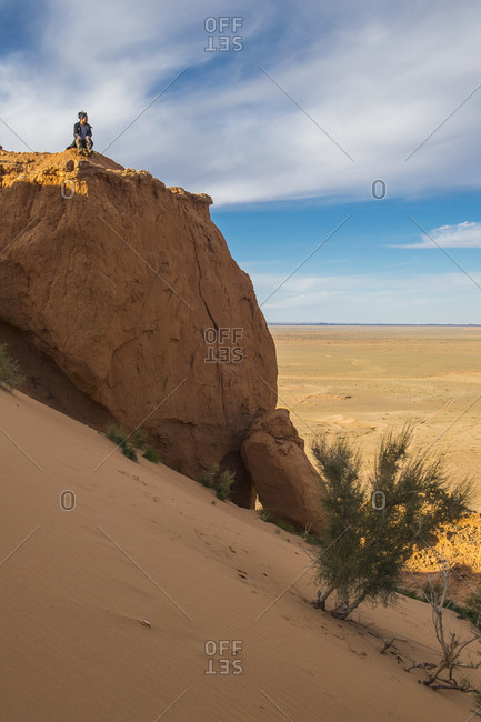 Woman at Bayanzag sandstone cliffs or flaming cliffs, Gobi desert, Mongolia