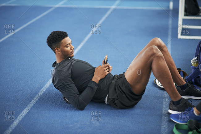 Runner texting while doing sit ups on indoor running track