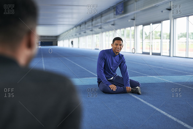Runners sitting on indoor running track