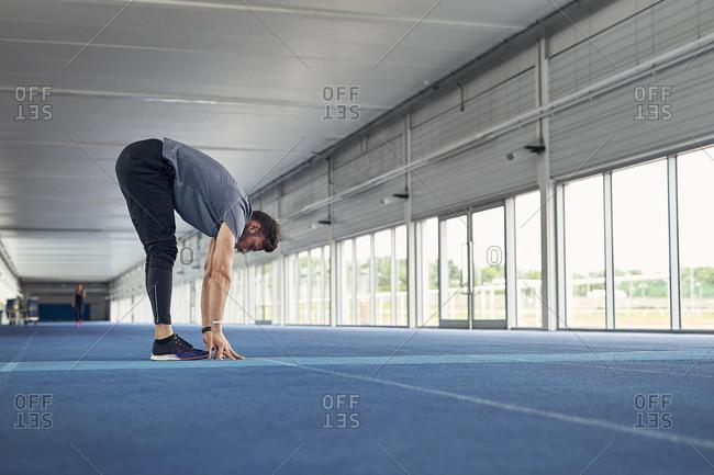 Runner stretching on indoor running track