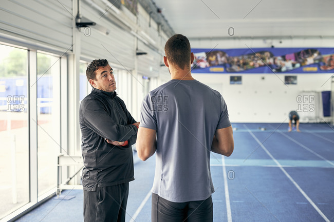 Coach and runner speaking in indoor running track