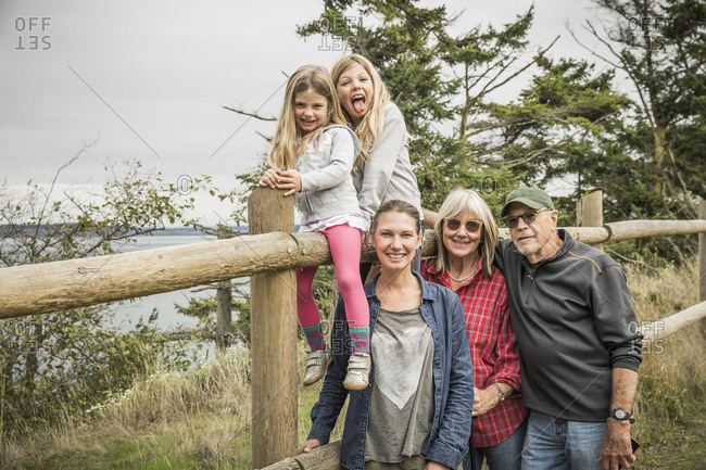 Girls sitting on fence with mother and grandparents, Port Townsend, Washington, California, USA