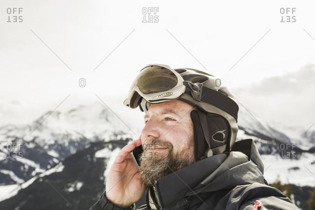 Mature male skier making smartphone call on snow covered mountain, Gerlos, Tirol, Austria
