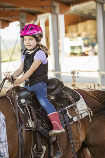 Girl horse riding in equestrian arena
