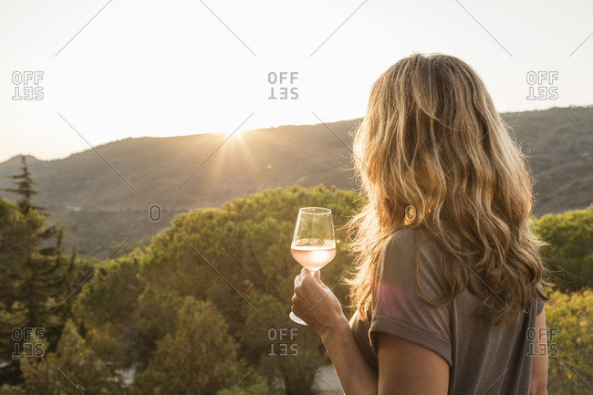Mature woman holding glass of wine watching sunset over hills, rear view, Portoferraio, Tuscany, Italy