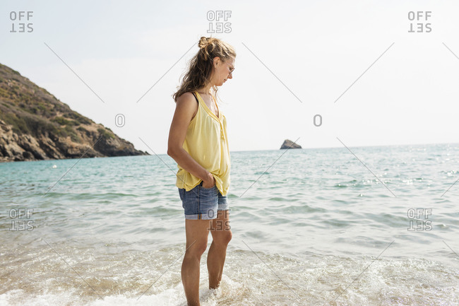 Mature woman standing ankle deep in sea, Portoferraio, Tuscany, Italy