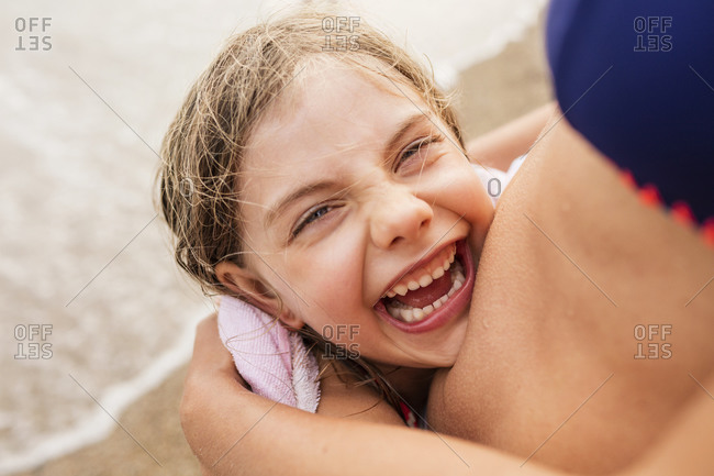 Laughing girl being hugged by mother on beach, Portoferraio, Tuscany, Italy