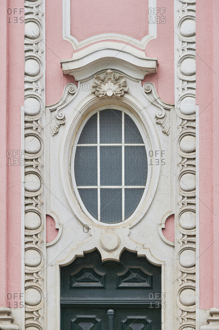 Oval window on a pink building in Lisbon, Portugal