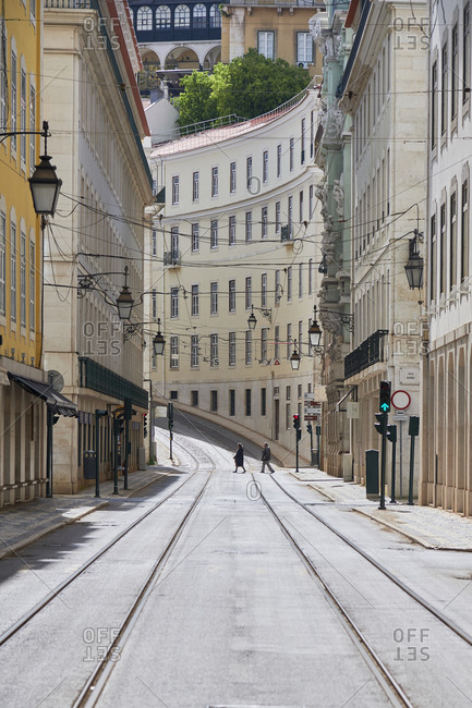 Two people in the distance on empty street, the rua da Conceicao in Lisbon during the pneumonia outbreak by the new Coronavirus