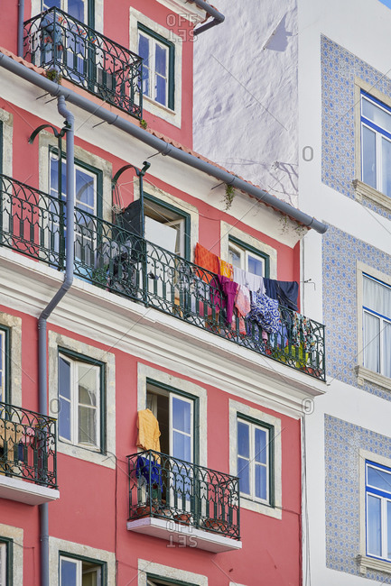 Laundry hanging from balconies on pink apartment in the Arroios neighborhood