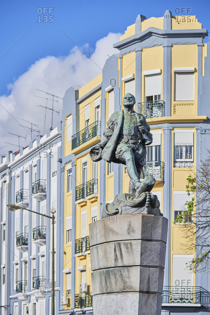 Colorful facades of apartments behind statue in the Arroios neighborhood of Lisbon, Portugal