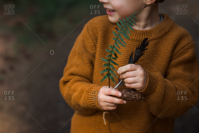 Little boy holding fern leaves, a feather and pinecone