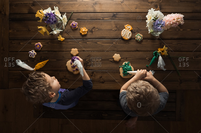 Overhead view of little boys decorating cookies on a wooden table with spring flowers