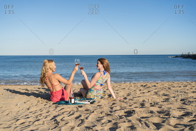 Happy girlfriends smiling and clinking glasses of wine during picnic sitting on sandy beach