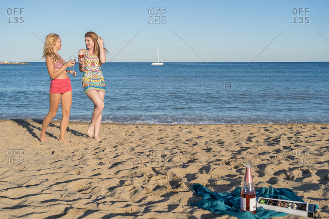 Full length delighted women with glasses of wine smiling and speaking with each other while walking on sandy shore near sea on resort